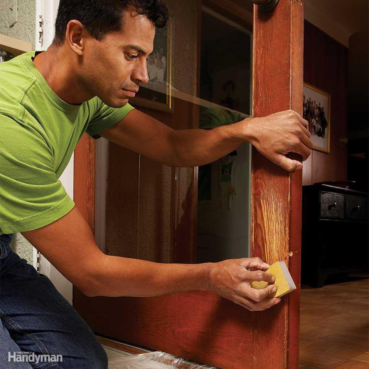 Man wiping over claw marks in a door