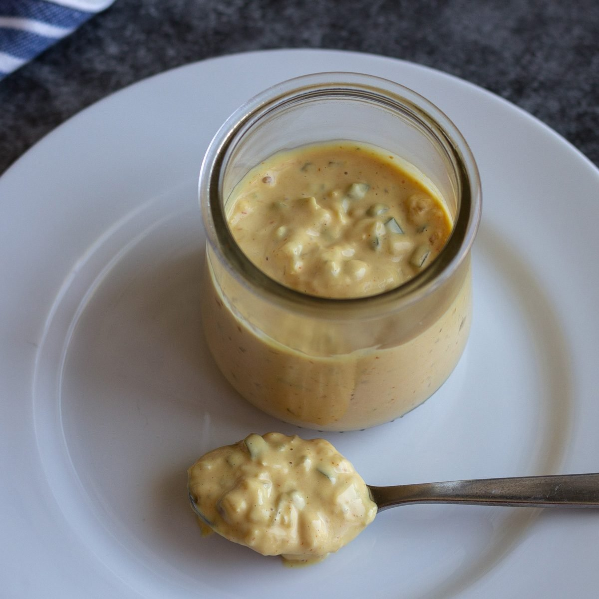 Glass jar with Big Mac Sauce on a white plate with a spoonful of sauce as well.