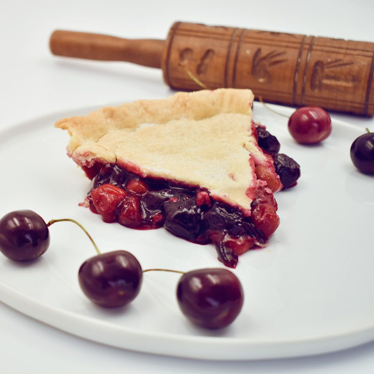 Slice of cherry pie beside a rolling pin