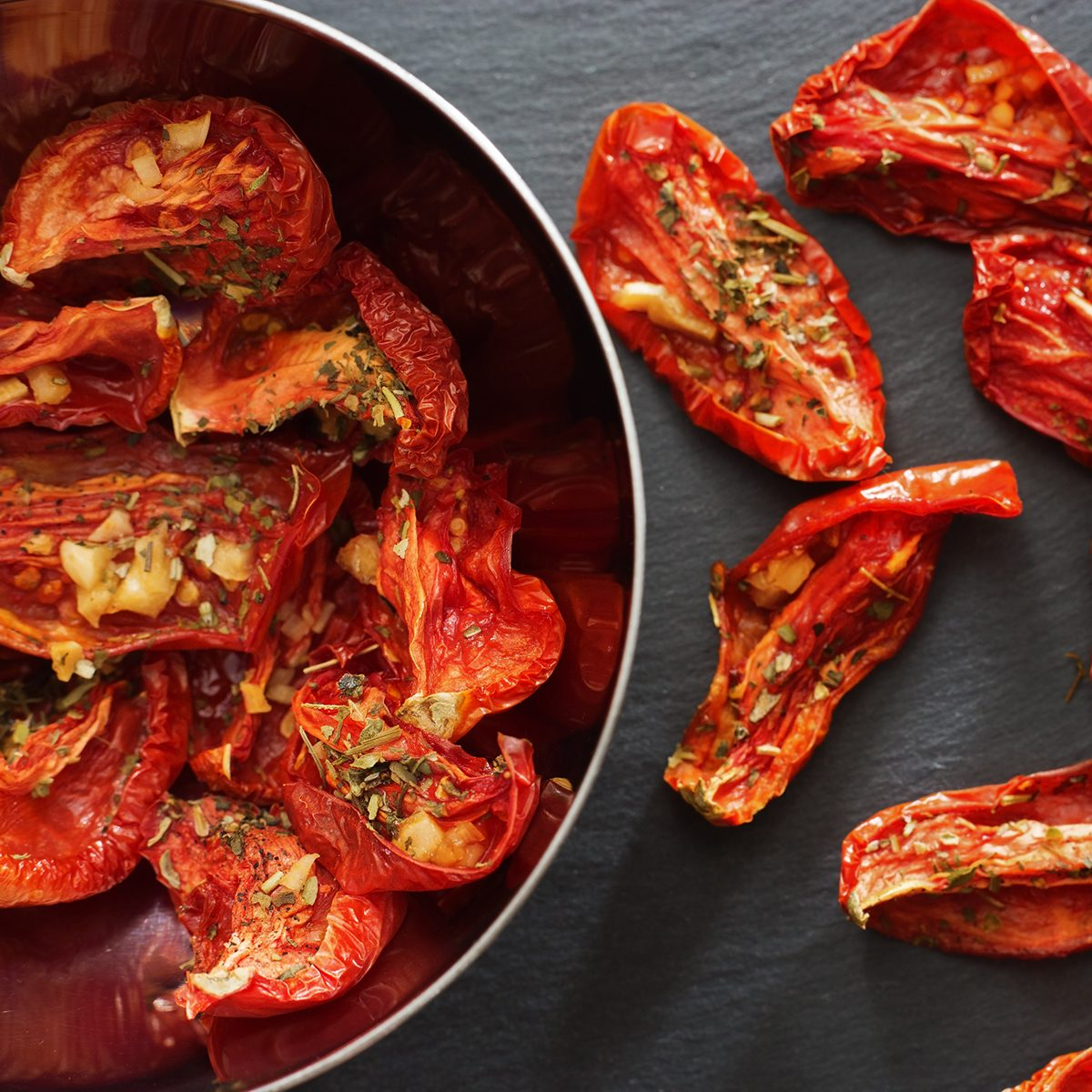 Tomatoes sun-dried in small pieces lying in a metal dish on a dark background.