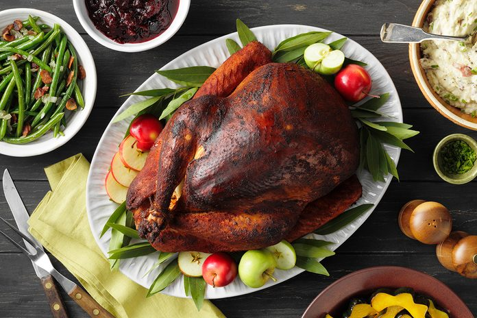 A smoked turkey on a platter arranged beautifully on a Thanksgiving table.