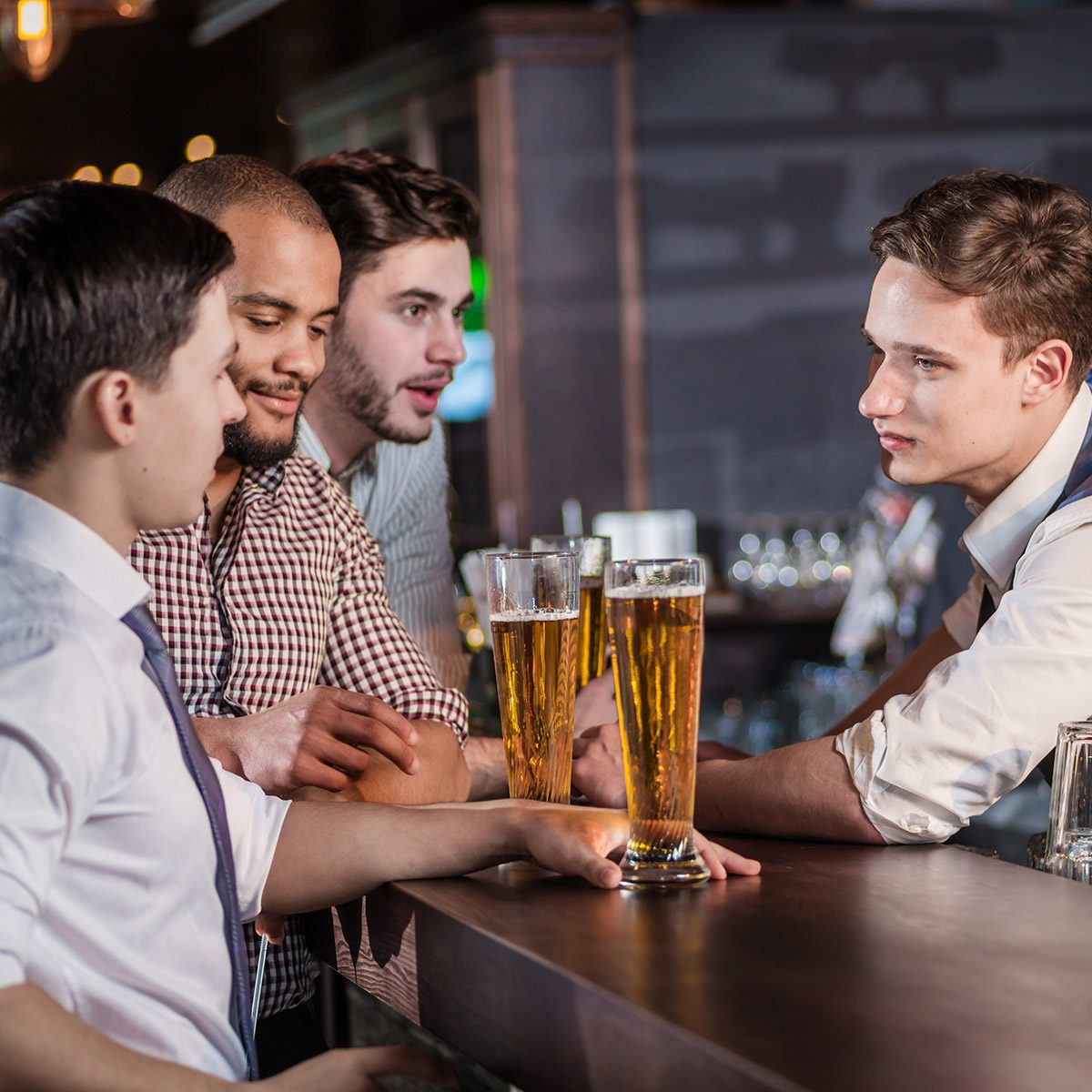Acceptance of the order at the bar. Three cheerful friend makes ordering a beer from the bartender