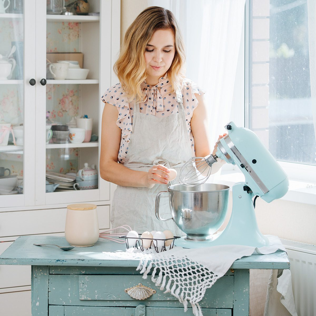 beautiful girl preparing dough in a food processor while standing in a bright kitchen
