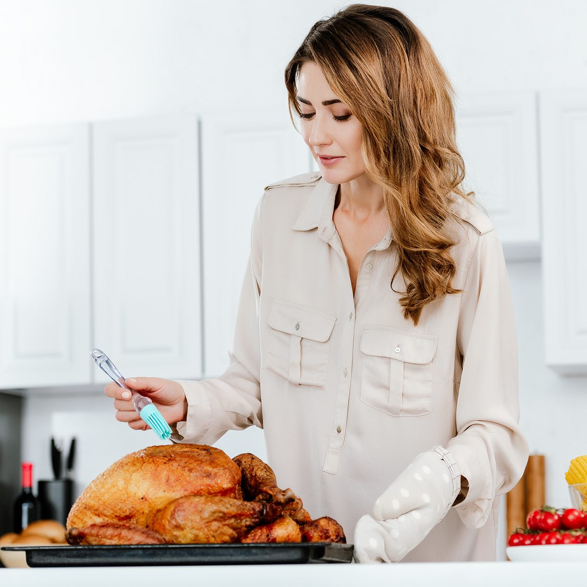 beautiful happy woman cooking thanksgiving turkey at kitchen