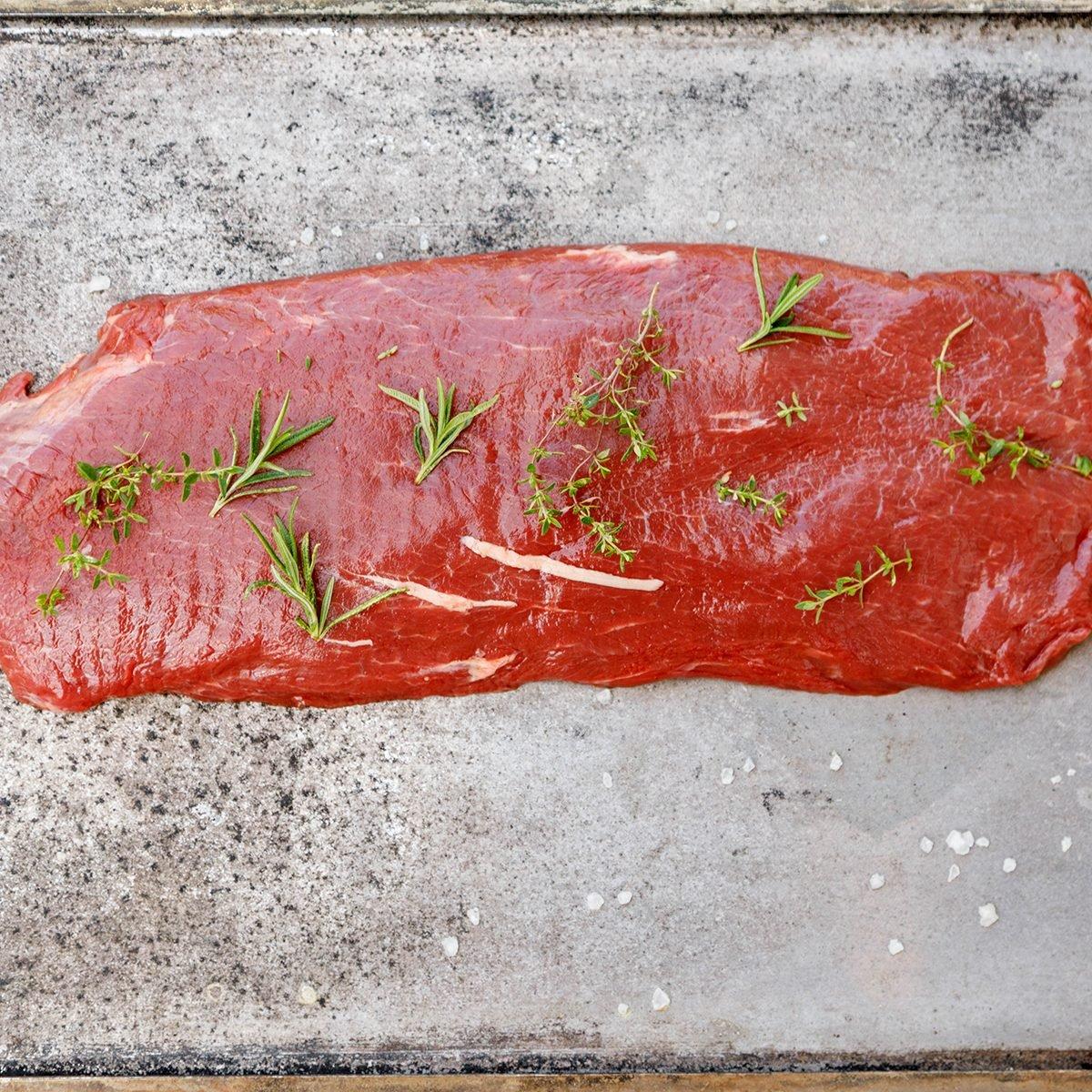Beef Flat Iron steak on old metallic smoke tray on white background