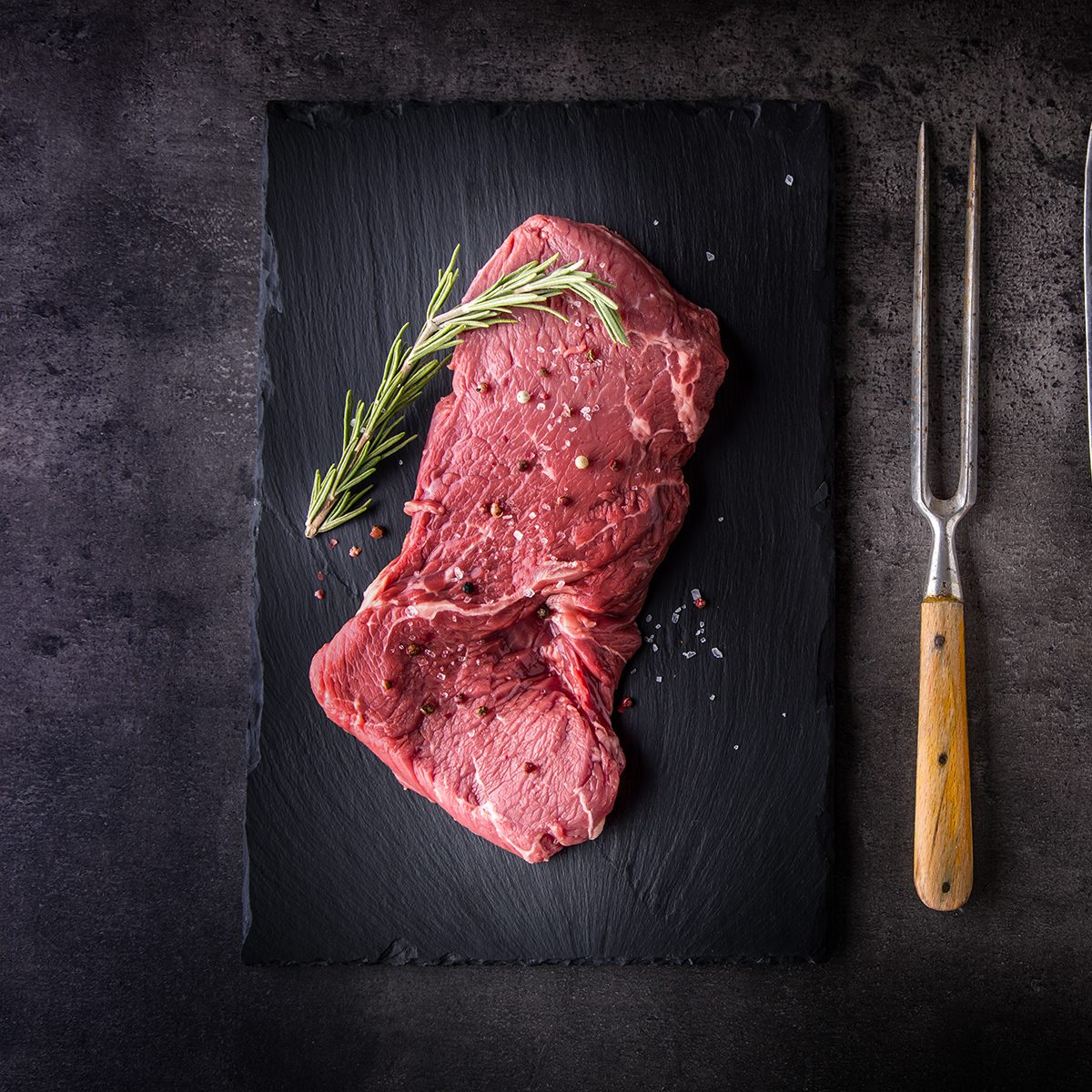 Beef raw rump steak with salt pepper rosemary butcher and fork.