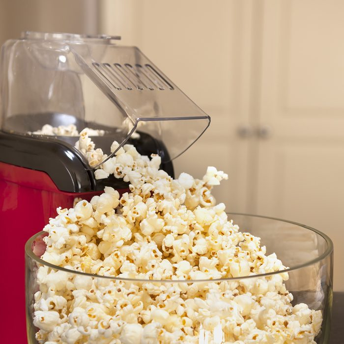 Bowl of popcorn with popcorn machine on a kitchen bench.