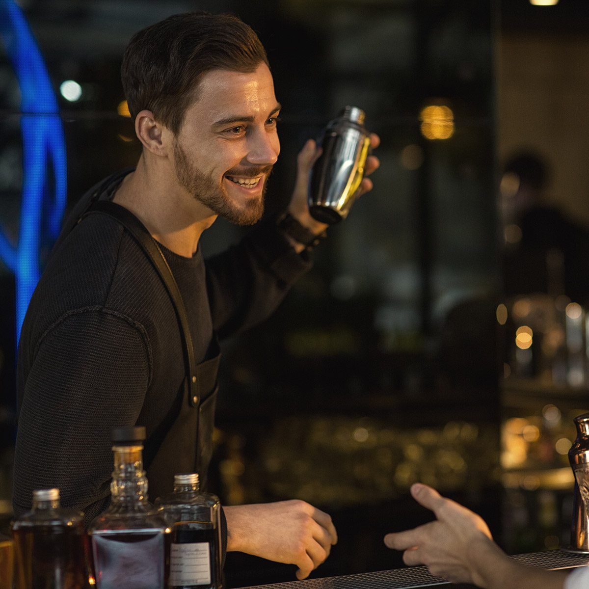 Cheerful handsome young male bartender working preparing cocktails at the bar talking to his male client smiling joyfully communication relationships party friendly service positivity worker job
