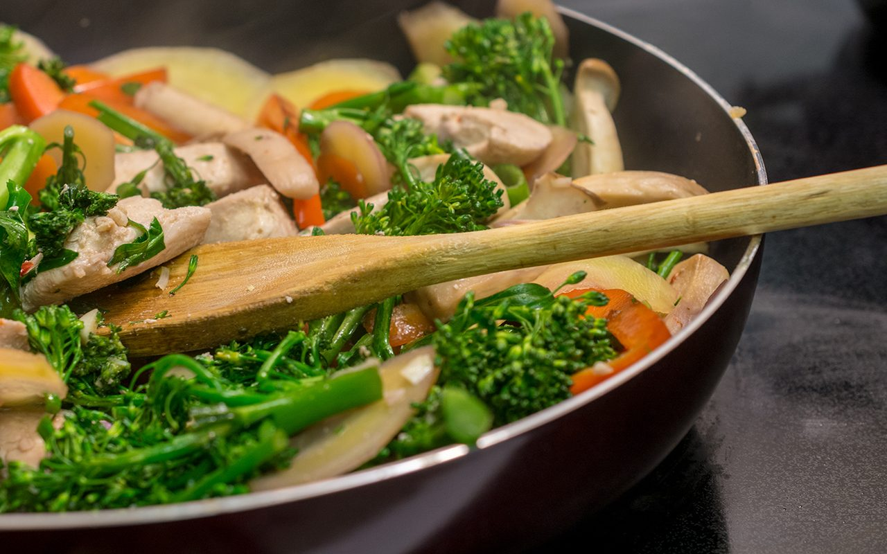 Close-up and side view of wooden spoon stirring chicken and vegetables in cast iron skillet