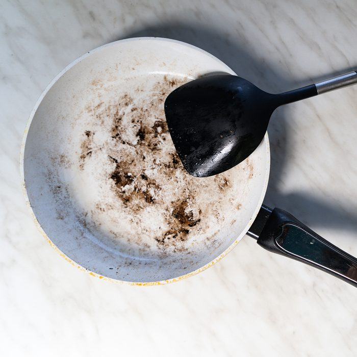 Dirty white frying pan and a plastic spatula