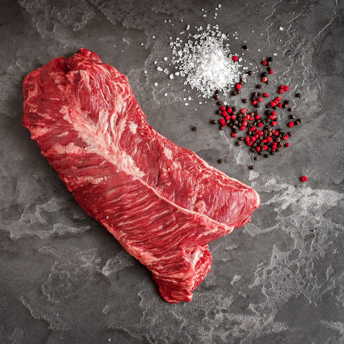 Hanging Tender steak on a stone background with salt and pepper