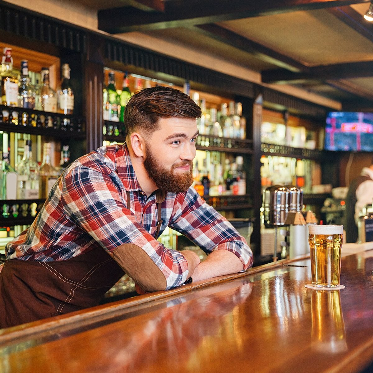 Happy attractive young barman giving glass of beer and talking to african american young man