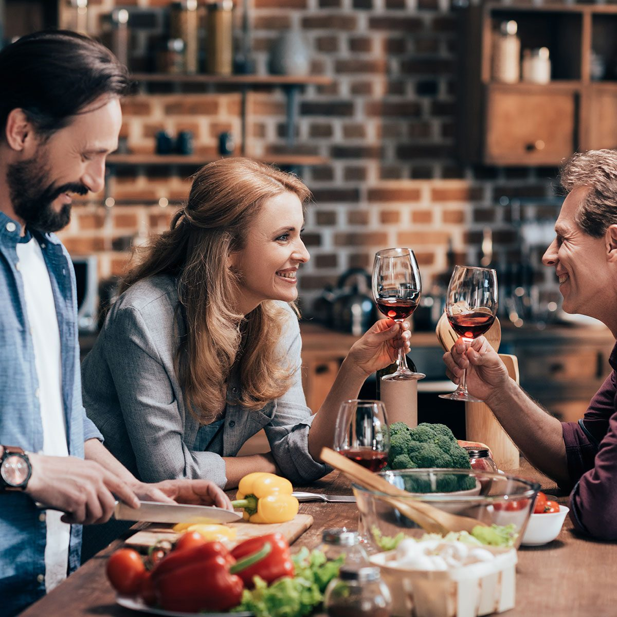 happy friends drinking wine and smiling each other while man cutting vegetables for salad