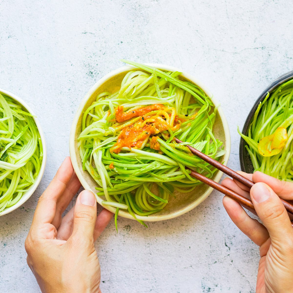 Homemade green zucchini spaghetti or pasta in bowl with chopsticks. Woman hands holds vegan, vegetarian healthy food.
