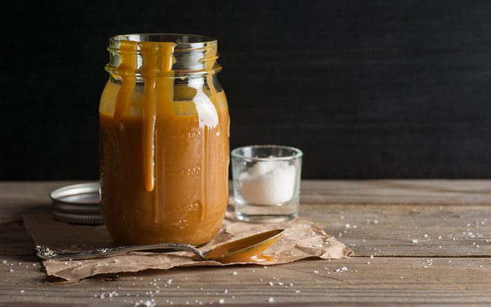 Homemade salted caramel sauce, in a jar, with a spoon.