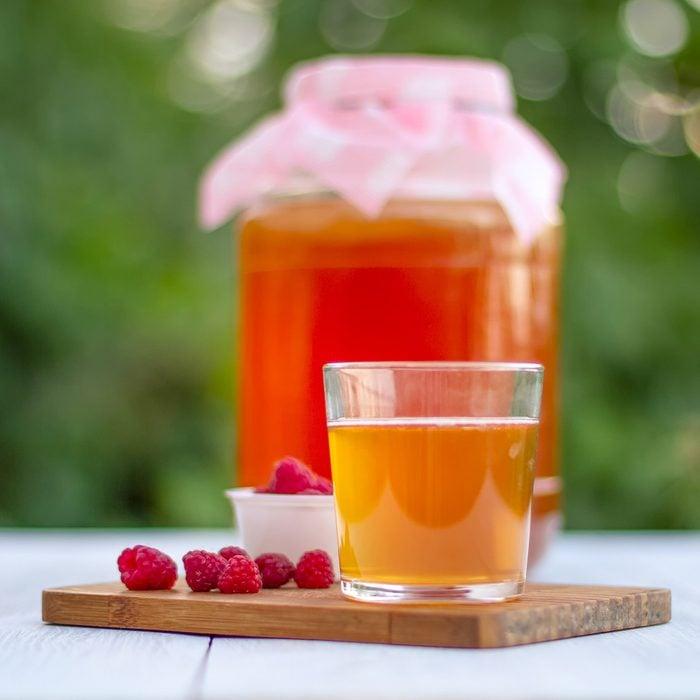 Glass jar with Kombucha, poured glass with Kombucha and raspberries in the summer garden.