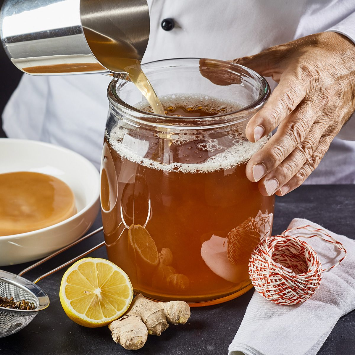 Man pouring a brew of sweetened black tea into a sterilised glass jar ready to add the scoby while making homemade kombucha