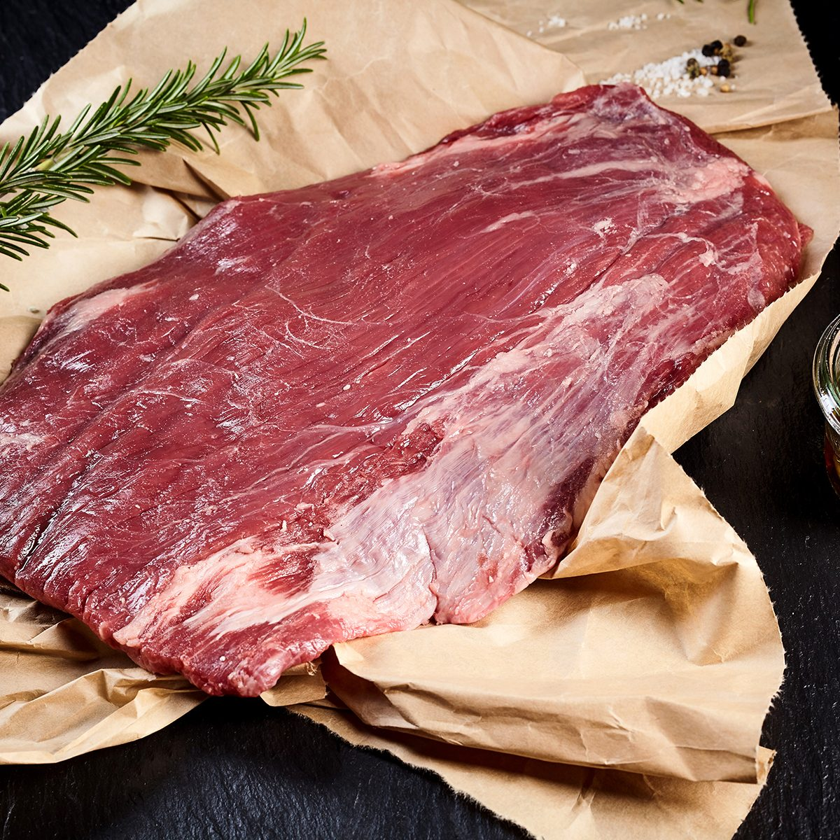 Portion of lean raw flank steak for roasting or grilling on crumpled brown paper in a rustic kitchen with a sprig of fresh rosemary and olive oil marinade