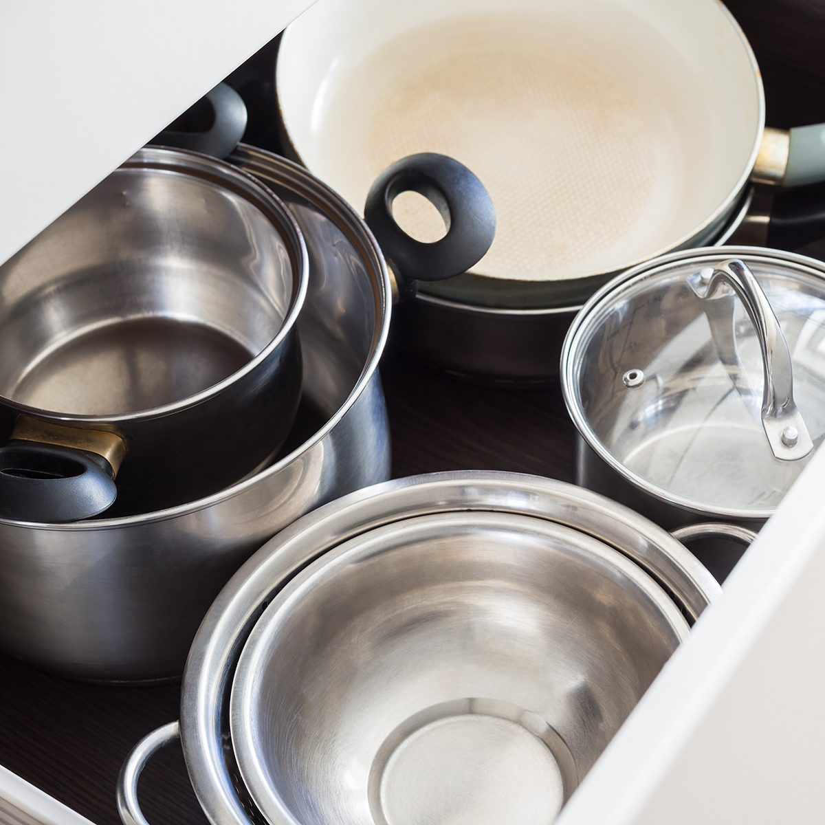 Open drawer of cabinet with steel pots and pans and bowl.