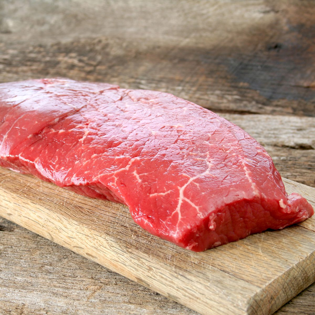 Raw beef on a cutting board ready to be cooked.