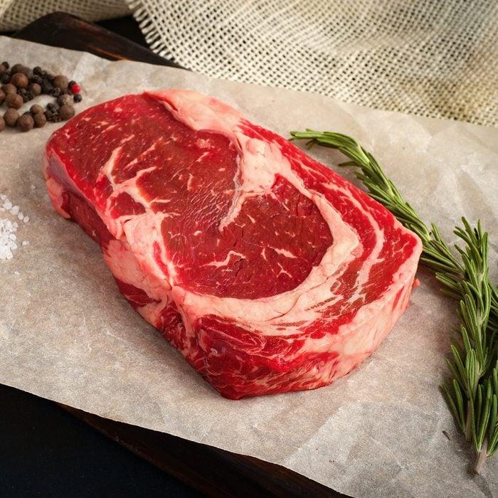 raw ribeye steak lying on Kraft paper around the pepper, salt, rosemary on a wooden Board