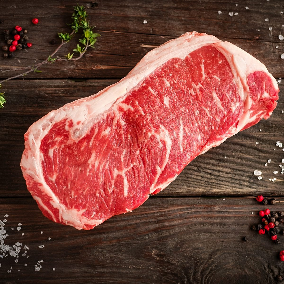 raw strip loin steak on white wooden background in rustic style with salt and herbs