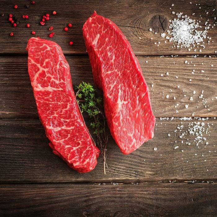 raw top blade steak on wooden background