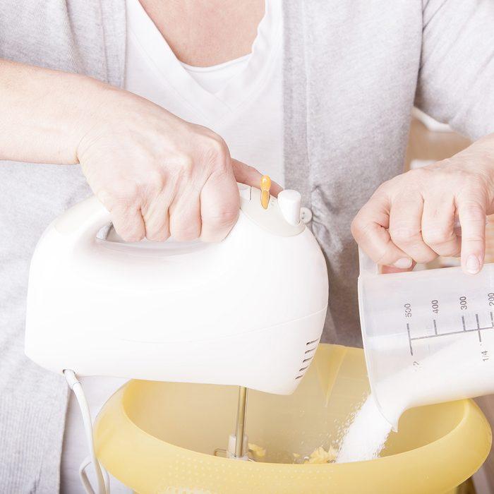 senior woman baking homemade chocolate cake,using a mixer and milk. baking chocolate/stracciatella cake in a glass jar.