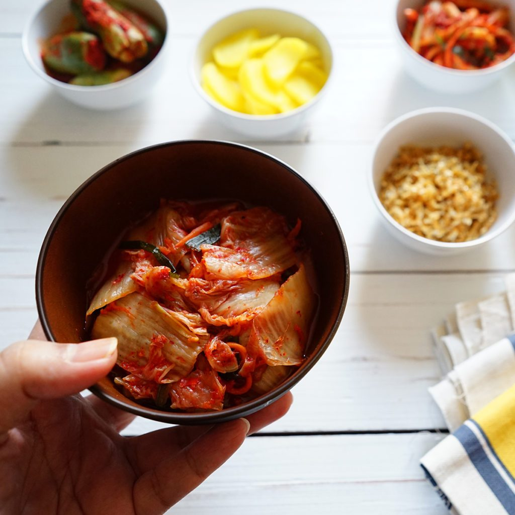 Hand holding bowl of Baechu Kimchi or traditional Napa Cabbage Kimchi over blurred background of colorful variety kimchi and Korean side dishes on white wood planks. Probiotic and fermented foods.; Shutterstock ID 1238289316