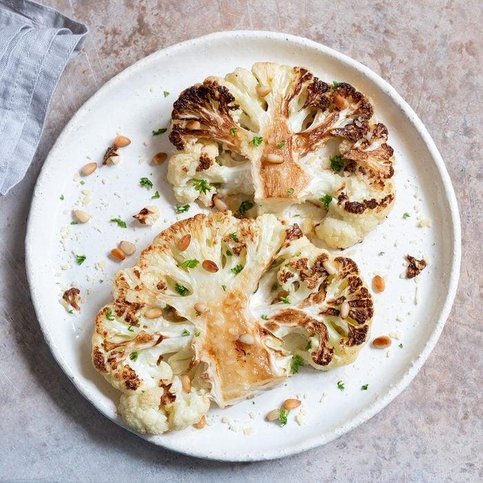 Vegetarian roasted cauliflower steak with pine nuts; Shutterstock ID 1342494923; Job (TFH, TOH, RD, BNB, CWM, CM): TOH