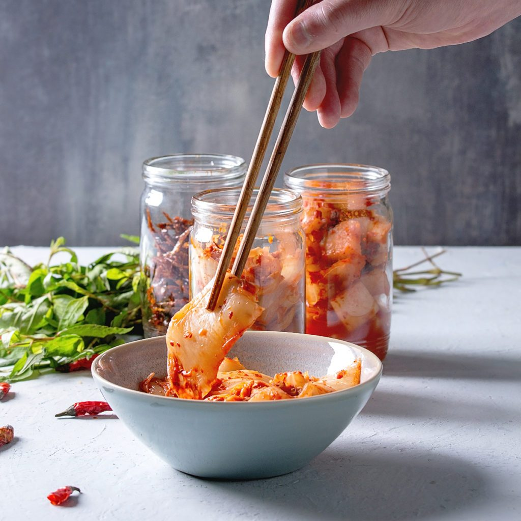 Korean traditional fermented appetizer kimchi cabbage and radish salad, fish snack served in glass jars with Vietnamese oregano and chili peppers over grey blue table. Chopsticks in mans hands.; Shutterstock ID 1345435652; Job (TFH, TOH, RD, BNB, CWM, CM): Taste of Home