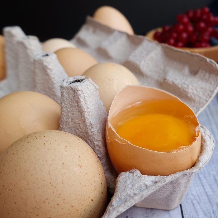 ingredients for baking lie on a light wooden background with a blue kitchen towel. flour, eggs, butter, berries, a bun and wooden tools; Shutterstock ID 1503991832; Job (TFH, TOH, RD, BNB, CWM, CM): TOH