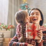 Merry Christmas and Happy Holidays! Cheerful mom and her cute daughter girl exchanging gifts. Parent and little child having fun near tree indoors. Loving family with presents in room.; Shutterstock ID 749009842; Job (TFH, TOH, RD, BNB, CWM, CM): Taste of Home