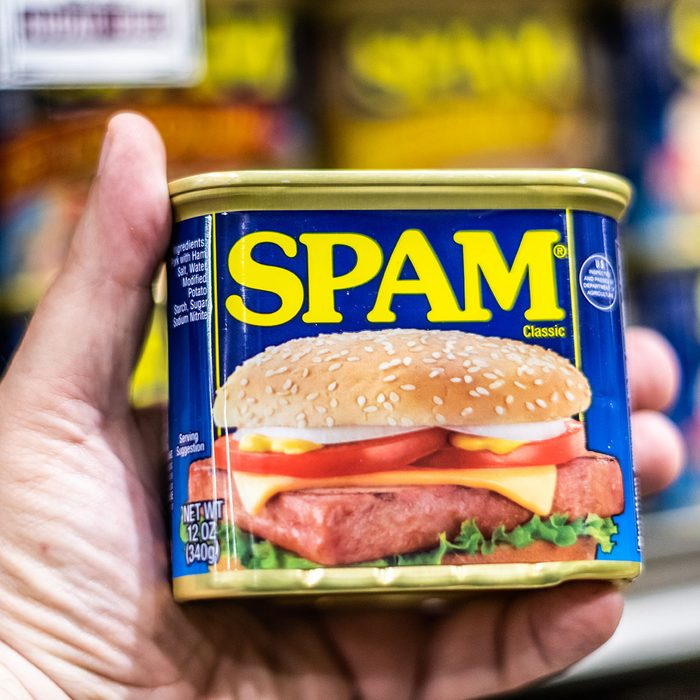 shoppers hand holding a can of SPAM brand canned meat