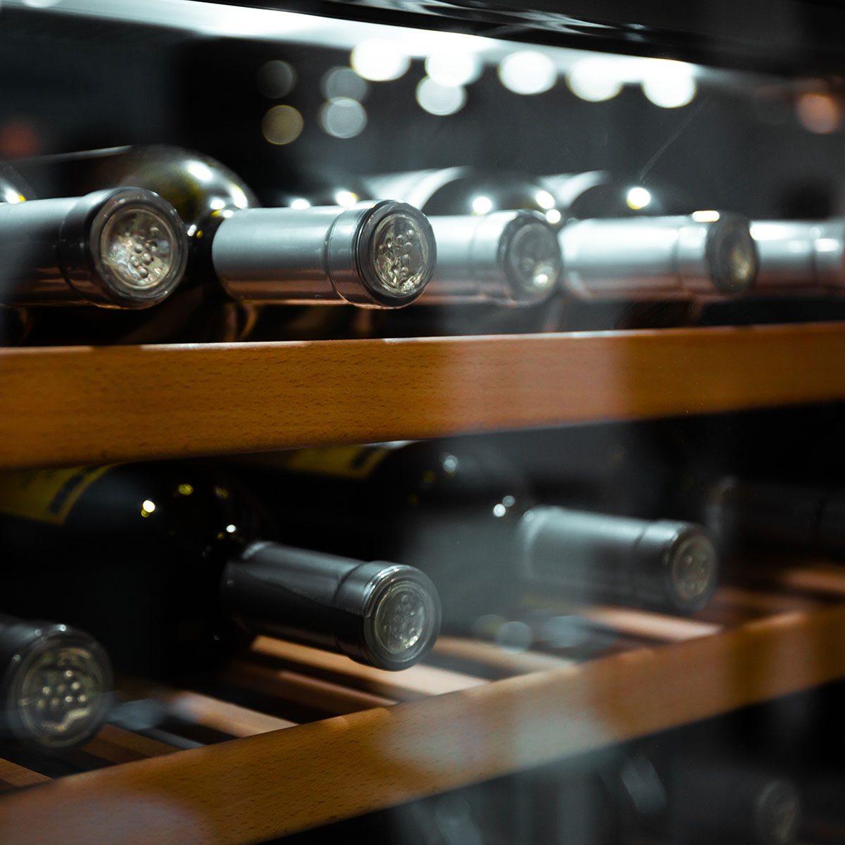 Storing bottles of wine in fridge. Alcoholic card in restaurant.