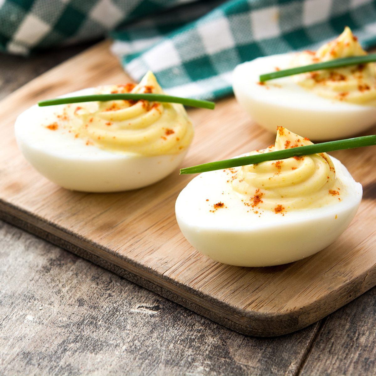 Stuffed eggs with mustard, mayo and paprika on wooden table