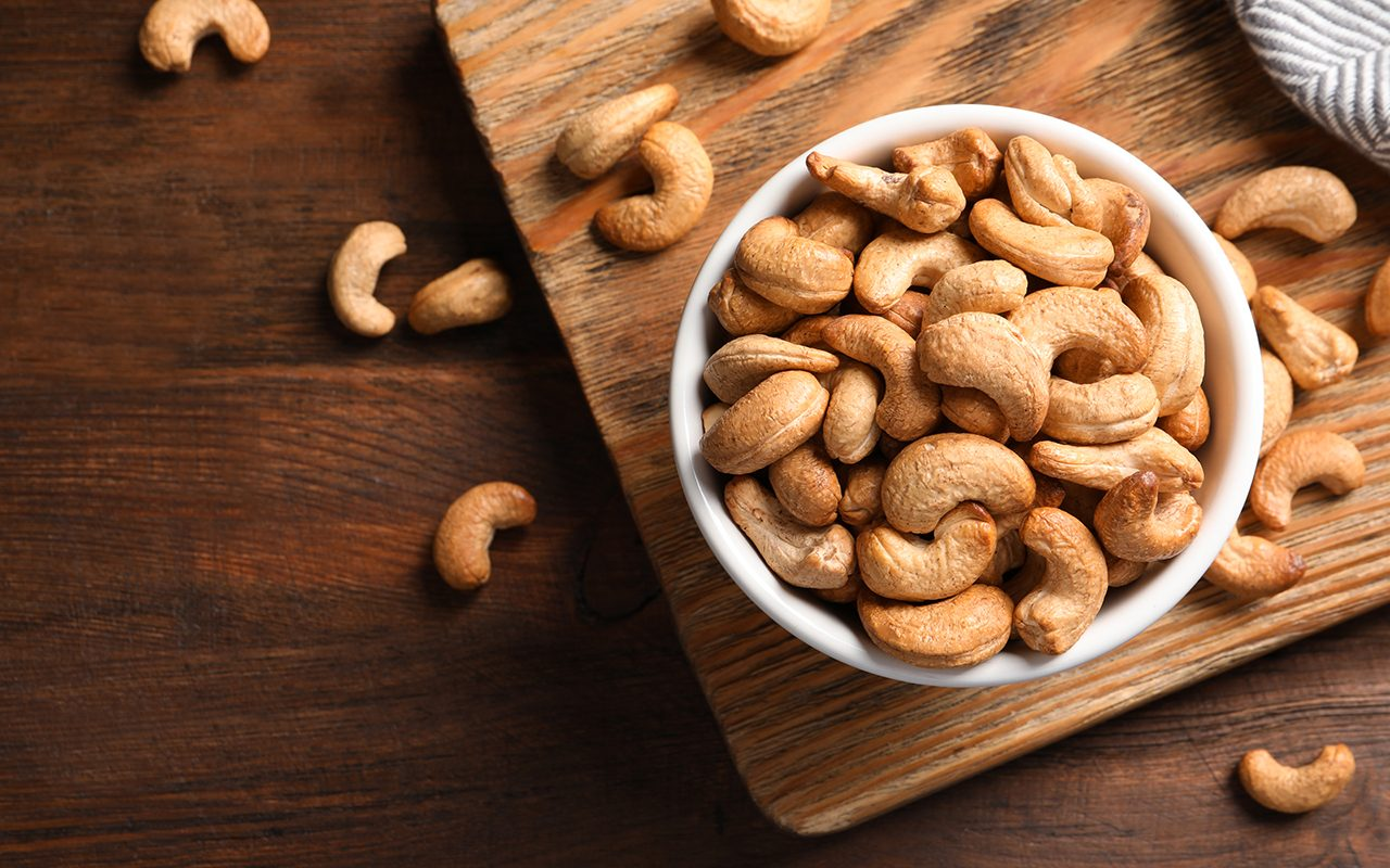 Tasty cashew nuts in bowl on wooden table, top view