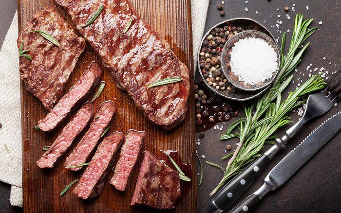 Top blade or denver grilled steak over cutting board.