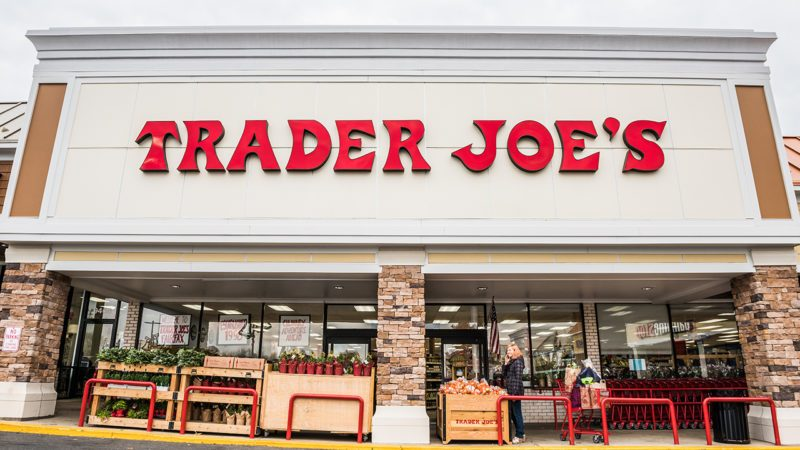 Trader Joes grocery store facade with sign and items on display and people walking