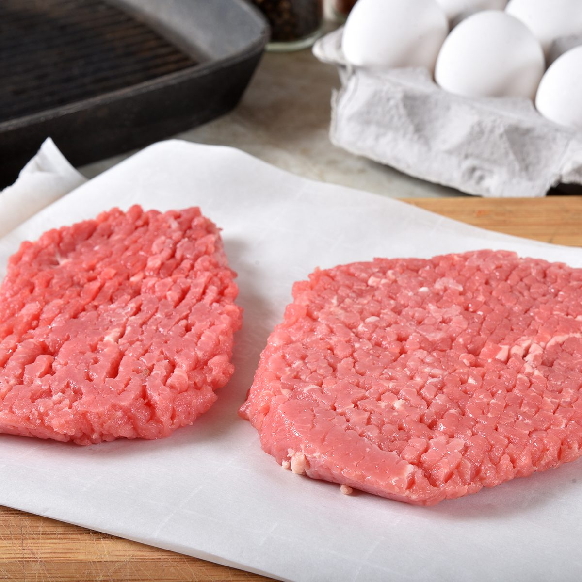 Uncooked cube steaks on a cutting board near a cast iron grill and a carton of eggs