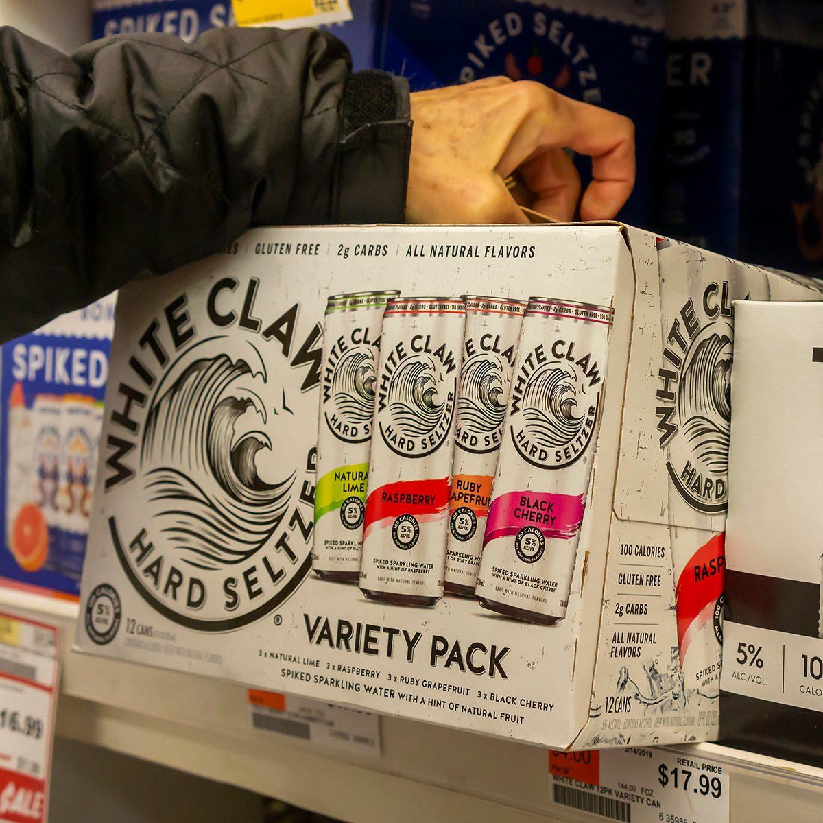 A discerning consumer chooses a case of White Claw brand hard seltzer among other brands in a cooler in a supermarket