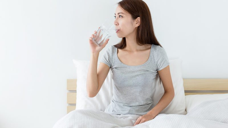 Woman drink a glass of water at morning