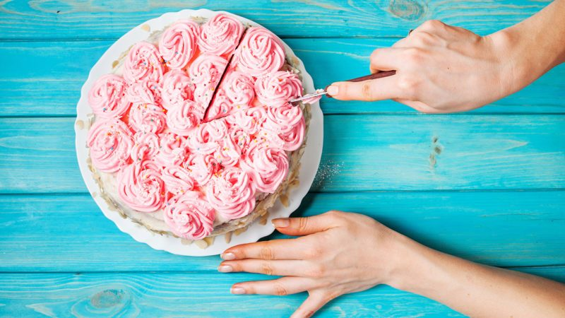 Woman's hands cut the cake with pink cream on blue wood background. Pink cake.
