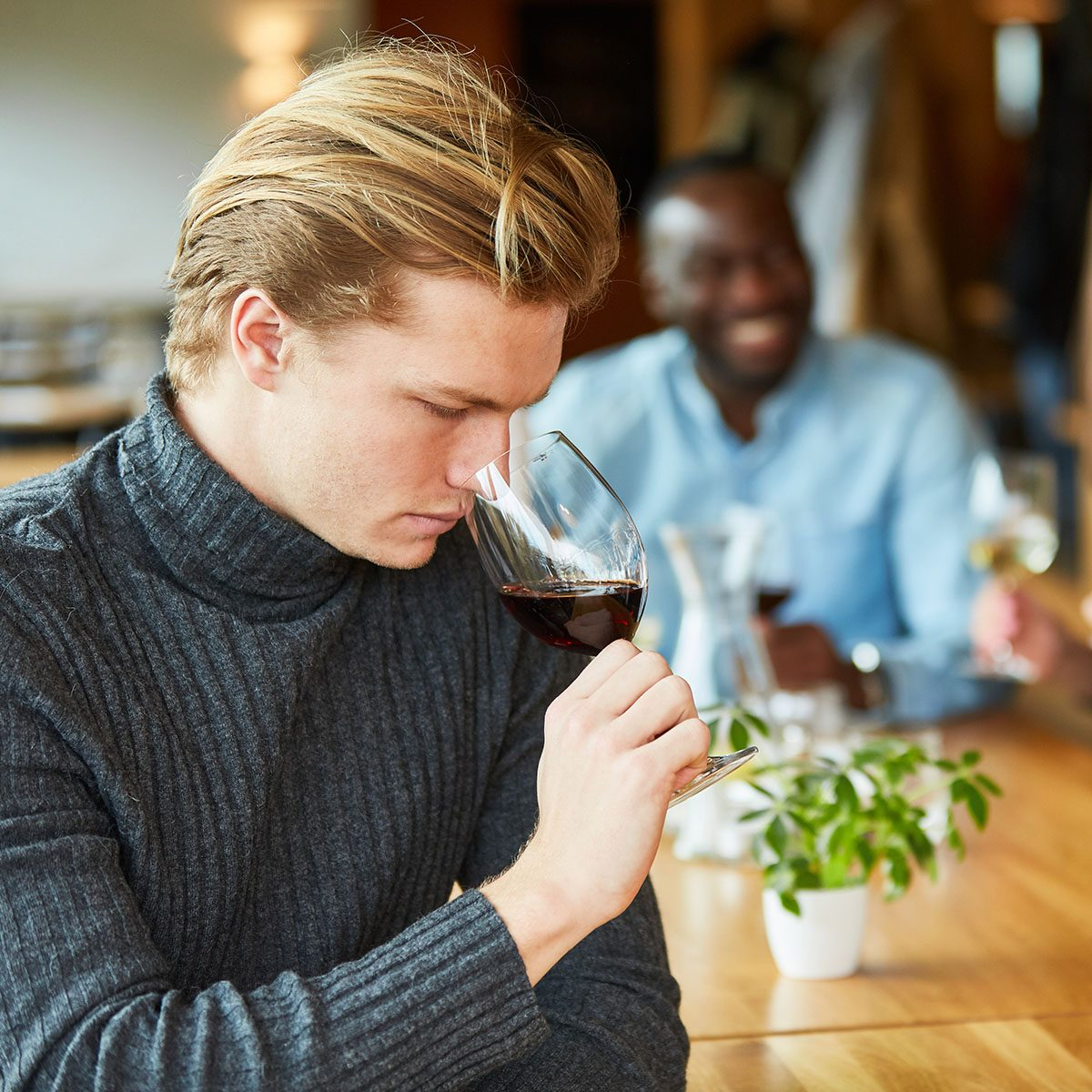 Young man at a wine tasting with a glass of red wine checks the bouquet