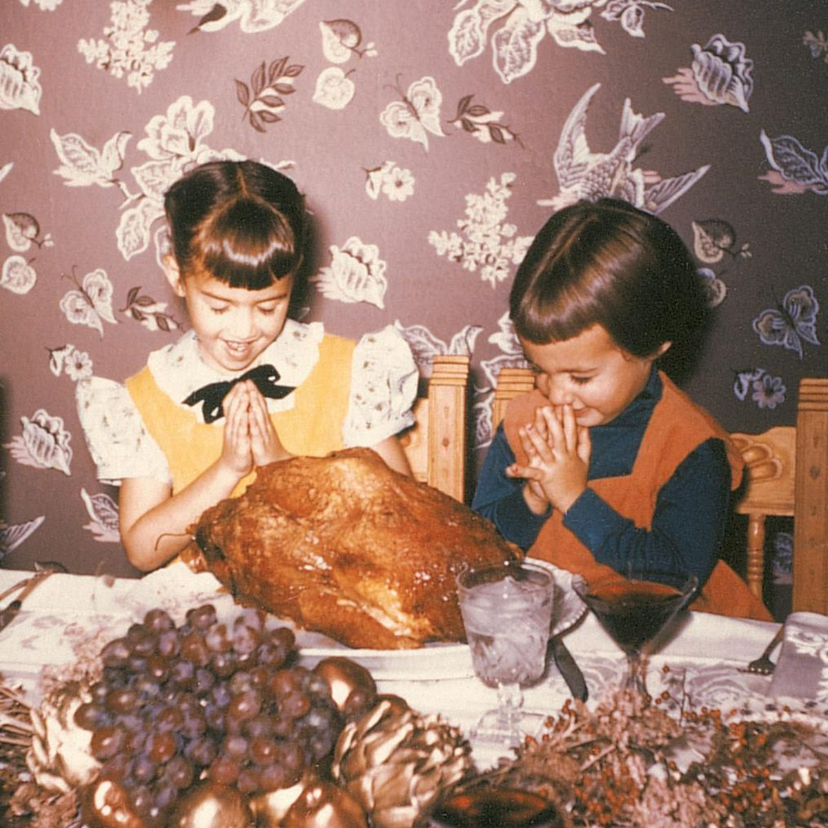 two 1950s sisters laugh while they prey for the turkey on the table