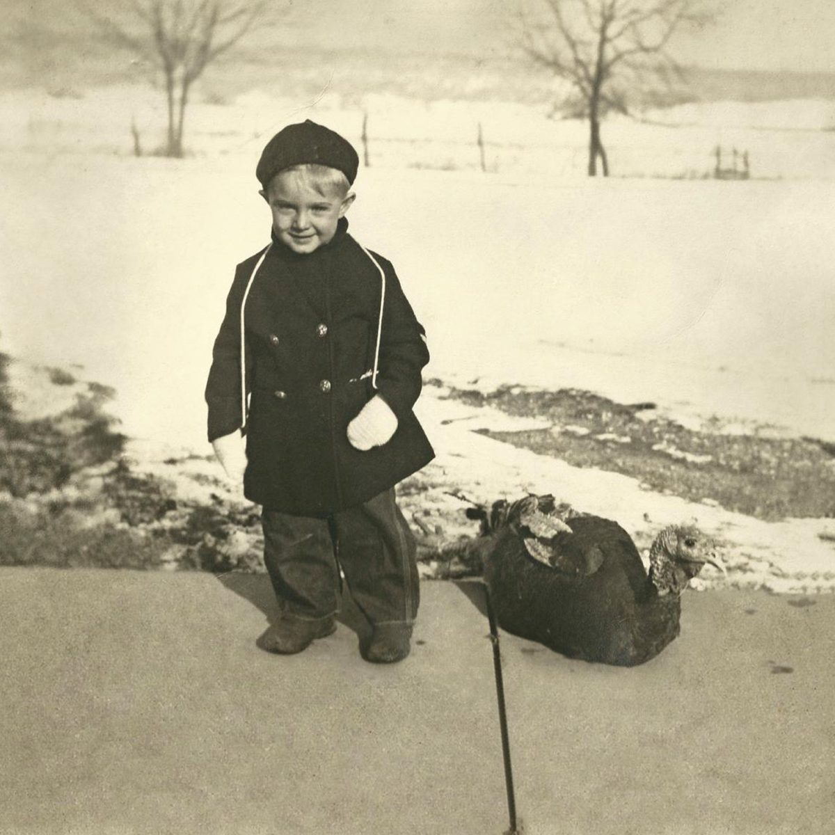 little boy froom the 1930s standing on snowy sidewalk next to a turkey