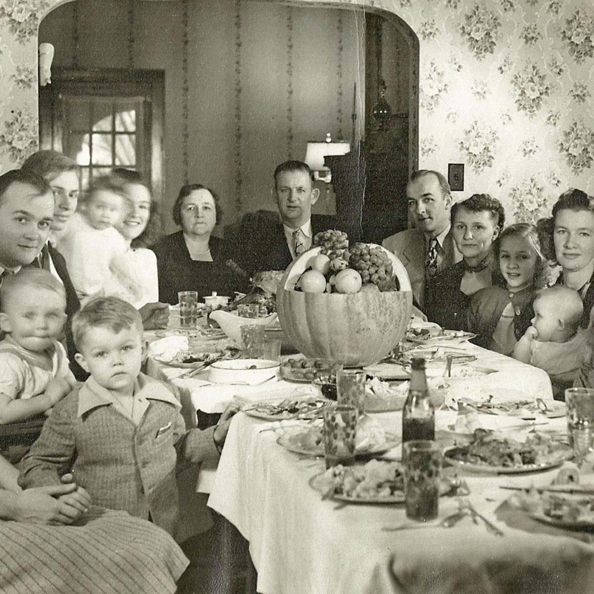 a very large family sitting around the table during thanksgiving dinner, looking at the camera, 1930s