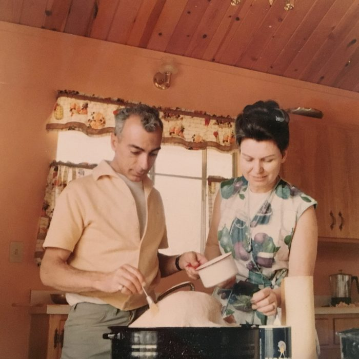 a man and woman prepare thanksgiving turkey in their cabin