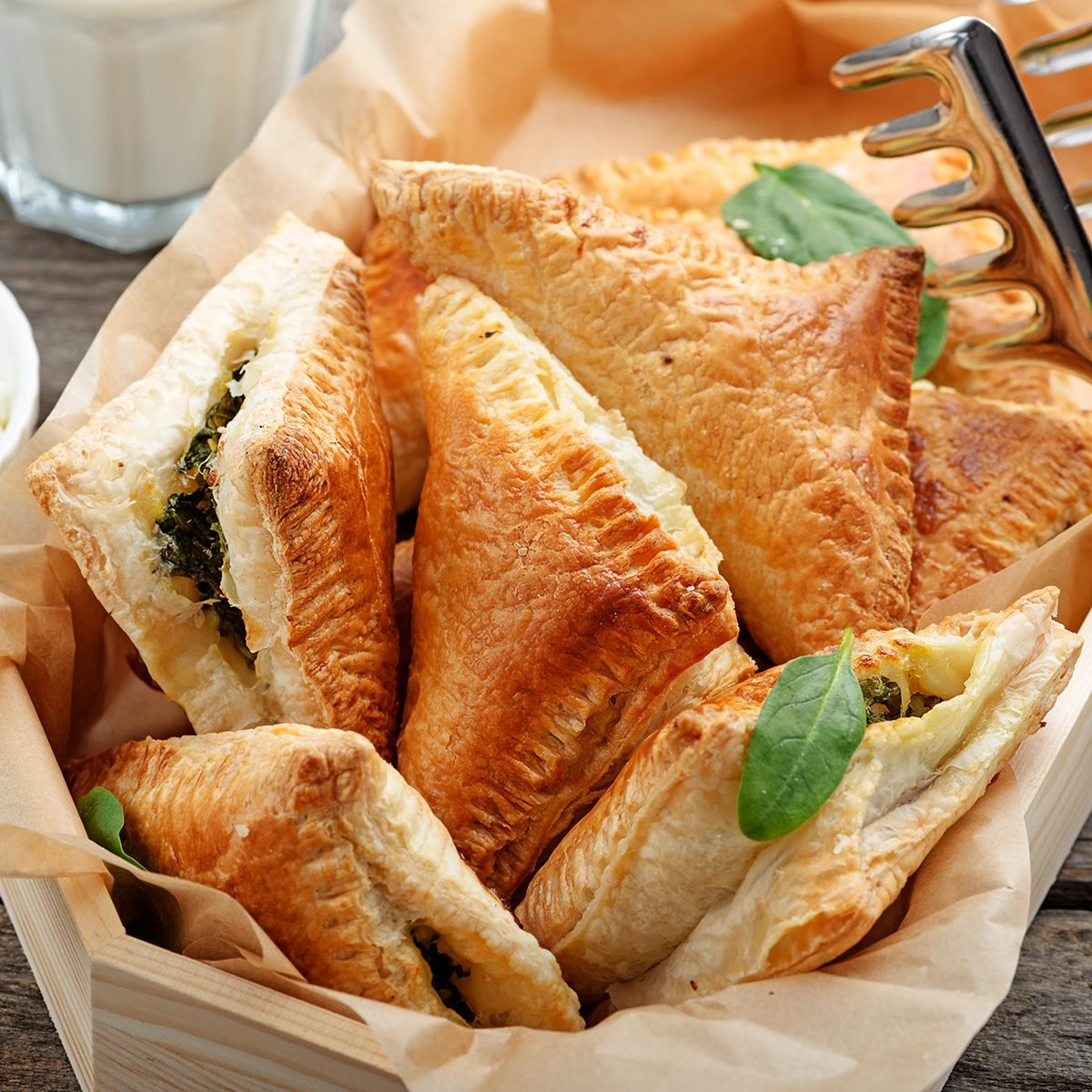 Puff pastry triangles filled with feta cheese and spinach on wooden table.
