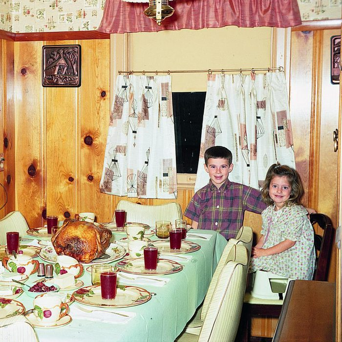 siblings sit at set dinner table in their retro 1960s kitchen